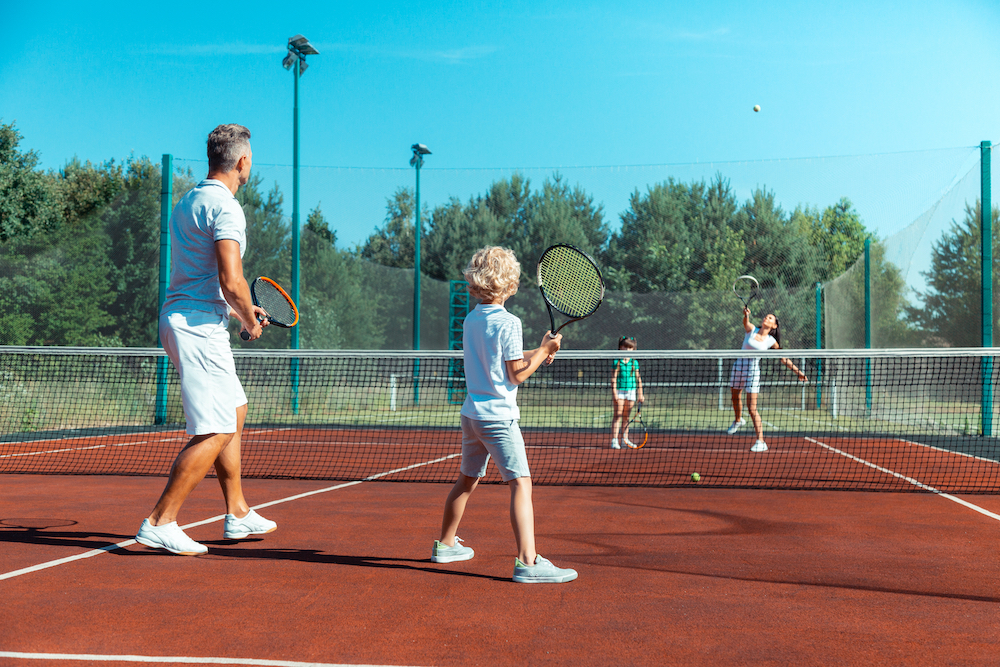 A family of four play tennis