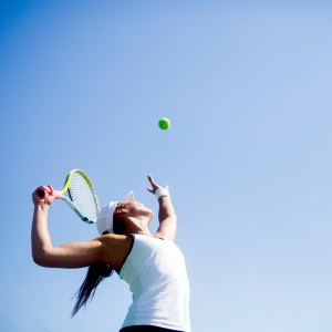 A woman is serving the ball. She is throwing the ball into the air with a tennis racquet in the other hand