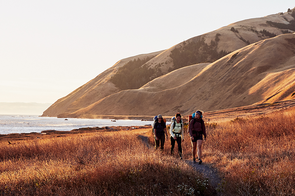 Three women are hiking along a scenic coastline