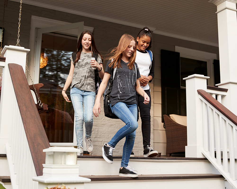 back-to-school image: three girls walking down porch steps
