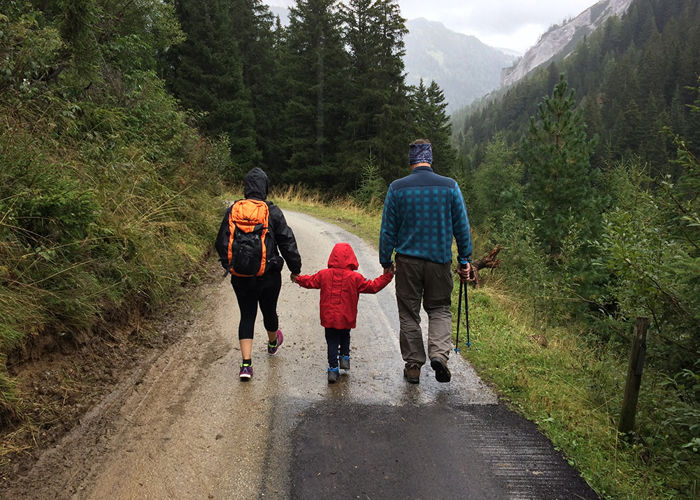 A family of three is hiking on a wet path. They are wearing jackets, active clothing and hiking shoes.